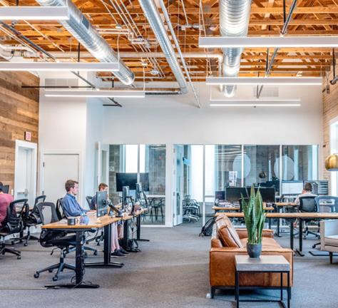 pessoas trabalhando em computadores em um amplo escritório